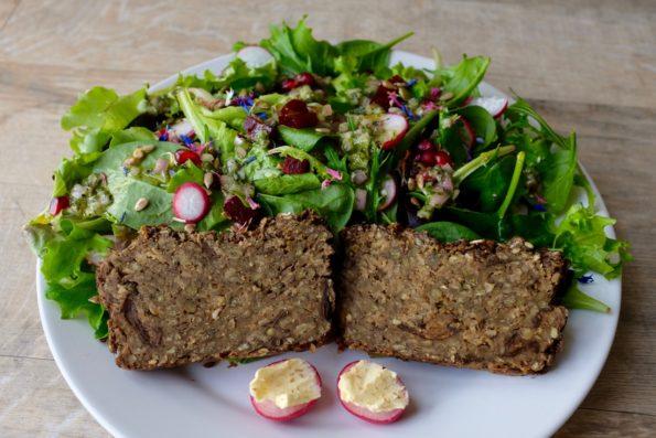Une belle salade verte avec deux tranches de la miche de lentilles et des petits radis